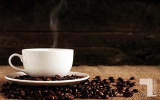湯気が出てるコーヒーカップとコーヒー豆