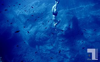 深い海を底の方へ泳ぐ人